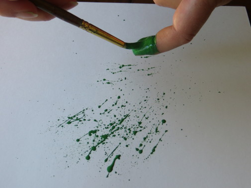 Load your brush with paint and flick it across your index finger to create the splatters for your splattered paint art-myflowerjournal